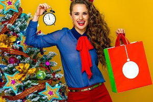 smiling woman with Christmas shopping bag showing alarm clock