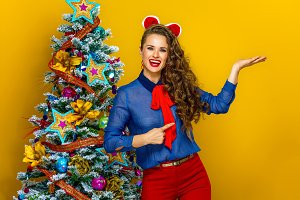 happy modern woman near Christmas tree pointing at empty palm