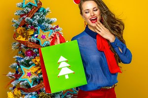 surprised elegant woman looking at Christmas shopping bag