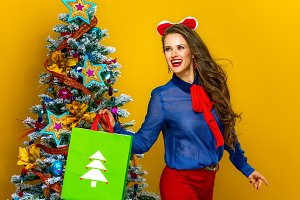 happy elegant woman with Christmas shopping bag looking aside