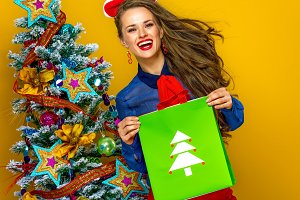 woman on yellow background holding Christmas shopping bag