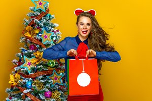 happy stylish woman with Christmas shopping bag