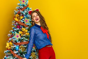 relaxed woman near Christmas tree isolated on yellow background