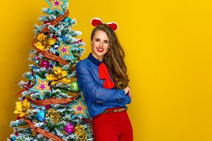 happy woman near Christmas tree isolated on yellow background