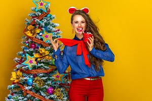 smiling woman with Christmas beverage on yellow background