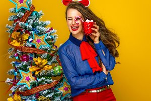 cheerful trendy woman with Christmas beverage