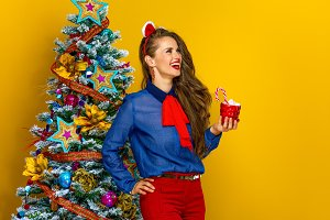 happy woman with Christmas beverage looking at copy space