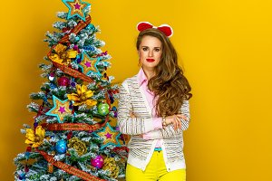 housewife near Christmas tree isolated on yellow background