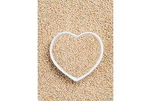 Quinoa in heart-shaped bowl on quinoa background