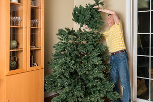 Senior man putting artificial christmas tree together for XMAS