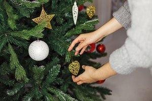 Girl decorates Christmas tree.