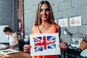 Happy young woman holding a picture of British flag drawn with watercolor technique during art therapy for adults