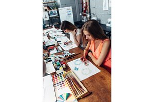 Two female designers working on new project drawing sketches with pencils