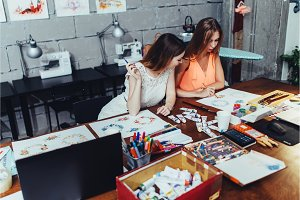Two female adult students drawing pictures with crayons sitting at desk covered with painting materials during classes in modern art school