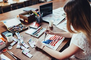 Young female illustrator drawing flag of the USA in using aquarelle paint sitting at workplace