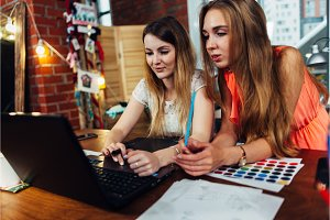 Two young women working on new creative design using laptop discussing ideas at cozy stylish studio