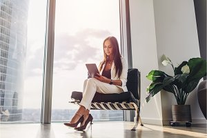 Successful woman wearing suit sitting on armchair using tablet computer at her loft apartment in city center