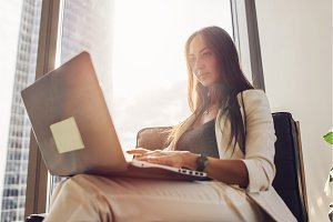 Young woman working on laptop sitting at home
