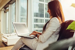 Side view of female boss wearing stylish elegant white suit holding laptop on her lap working in modern office