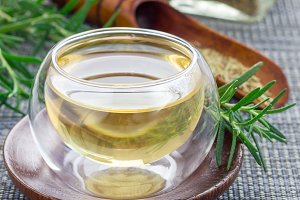 Herbal rosemary tea in a glass cup on oriental background, square