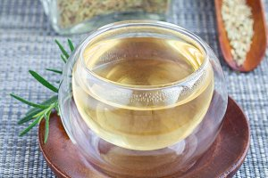 Herbal rosemary tea in glass cup on oriental background, square