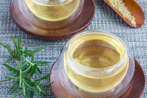 Herbal rosemary tea in a glass cup on oriental background, square format