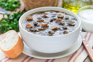 Black bean and ham soup in ceramic bowl on wooden table, horizontal