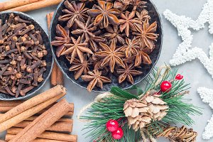 Different kinds of aromatic winter spices in bowls and on table, christmas decoration on gray concrete background, top view