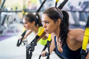 Fitness trx suspension straps training exercises women doing push-ups, working with own weith at gym.
