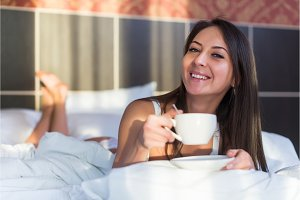 Beautiful woman lying in bed and drinking coffee or tea the morning
