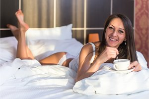 Beautiful woman lying in bed holding cup of hot coffee. Morning, smiling girl looking into the camera, waking up, having breakfast