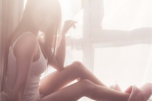 Woman looking at the sunrise sitting near window