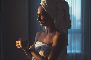 Naked woman with towel on her head and body drinking herbal tea after bath.