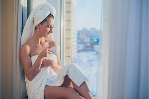 Romantic woman sitting before window and admiring sunrise or sunset with towel on her head body after bath.
