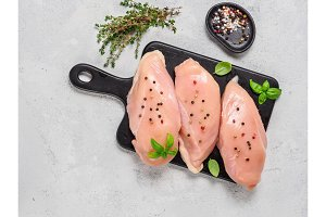 Raw chicken breast with fresh basil and thyme on black cuttingboard, copyspace