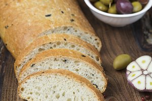 Italian ciabatta bread on board with herbs and olives