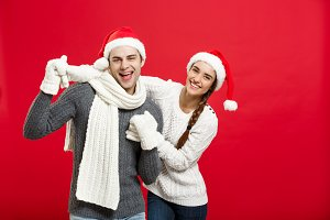 Christmas concept - Happy young couple in sweatesr celebrating christmas with playing and dancing.
