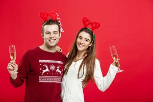 Christmas concept - Happy young couple in sweaters celebrating christmas with Champagne.