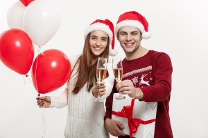 Christmas Concept - Young girlfriend holding balloon and champagne playing and celebrating with her boyfriend on Christmas day.