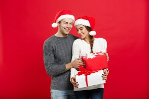 Christmas Concept -  handsome young boyfriend in Christmas sweater surprise his girlfriend with gifts.