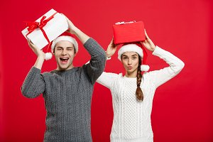 Christmas Concept -  portrait young couple in Christmas sweater enjoy playing with gifts.