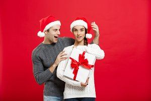 Christmas Concept -  handsome young boyfriend  in sweater surprise his girlfriend with white gift.