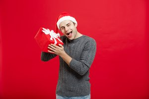 Christmas Concept -  handsome young man in sweater with red christmas gift.