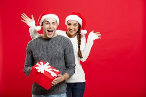 Christmas Concept - Young woman covering man's eyes with hand and giving surprise big gift. Isolated on Red background.