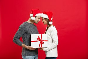 Christmas Concept - isolated lovely young couple holding tight with white gift over red background.