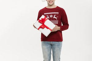 Christmas Concept - Full-length handsome young man in sweater with white christmas gift.