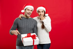 Christmas Concept -  portraiit young couple in Christmas sweater pointing finger gesture to gifts.