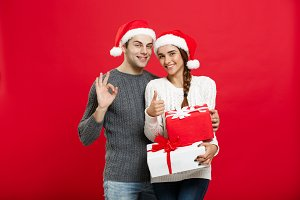 Christmas Concept -  portraiit young couple in Christmas sweater showing ok gesture with gifts.