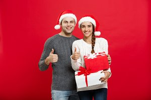 Christmas Concept -  portraiit young couple in Christmas sweater showing thump up with gifts.