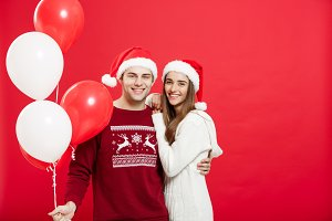 Christmas concept - Portrait of a romantic young couple with christmas balloon over red studio background.